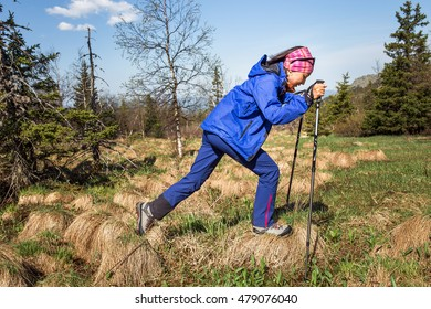 woman Hiking and jumping through a tussock in swamp