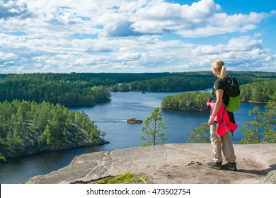 Woman hiking and looking lake landscape on high cliff in nature park in Finland