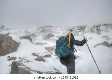 Woman hiking mount Katahdin during winter snow storm, Maine, USA