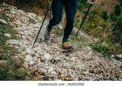 Woman hiking in mountains, legs and nordic walking poles closeup in autumn nature