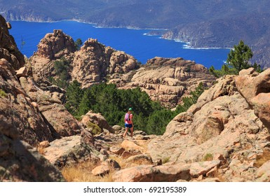 Woman hiking on a trail in the mountains of Corsica, France.