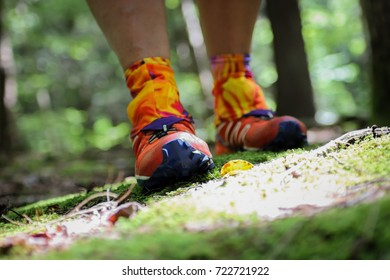 A woman hiking with orange sneakers in the woods