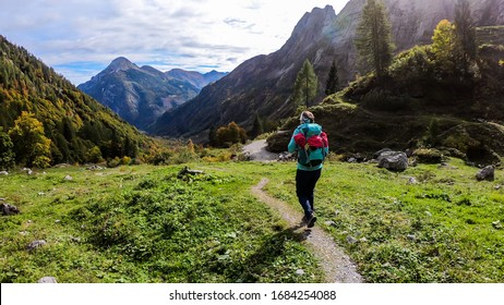A woman in hiking outfit wandering in Italian Alps. Sharp slopes on both sides of the valley. Hard to reach mountain peaks. There are many mountain ranges in the back. Serenity and calmness. Freshness