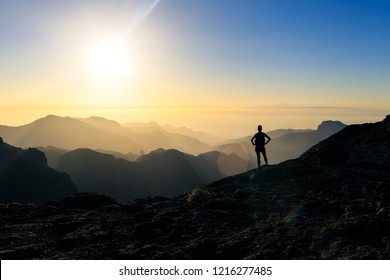 Woman hiking silhouette in mountains, sunset and ocean. Female hiker looking at beautiful inspiring view, sunset inspirational landscape.