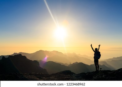 Woman hiking silhouette in mountains, sunset and ocean. Female hiker with arms outstretched on mountain top looking at beautiful night sunset inspirational landscape.