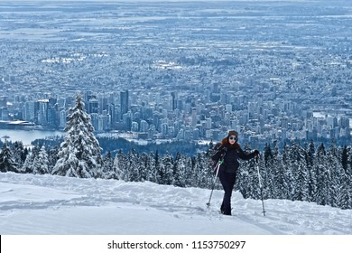 Woman hiking snowshoeing near North Vancouver on Cypress Mountain ski resort in winter. View of Vancouver downtown from above mountains. Beautiful British Columbia. Canada.