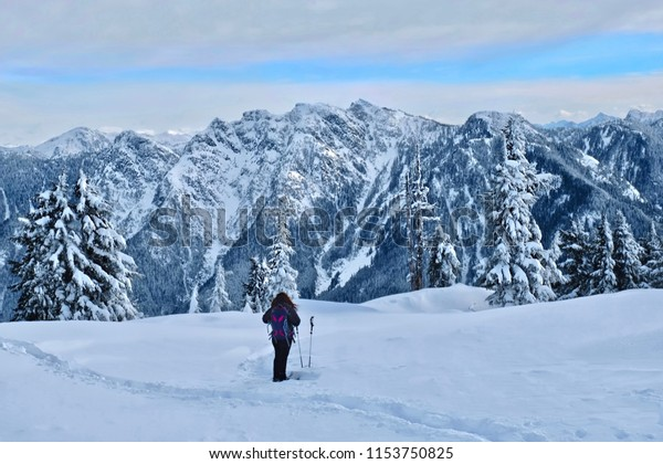 Woman hiking snowshoeing in North Shore mountains near Vancouver. Cypress Mountain Ski Resort in winter. Trees covered with fresh snow after snowstorm. British Columbia. Canada.
