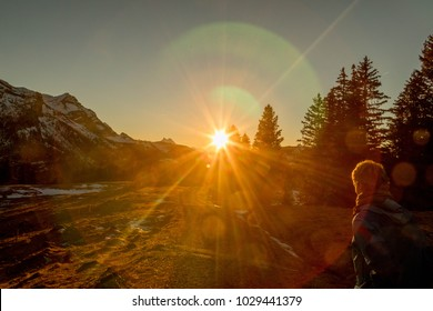 Woman Hiking Snowy Mountain at Sunset