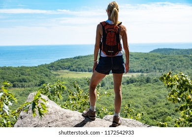 A woman hiking taking in a view.