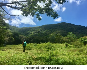 Woman hiking through an open field towards a mountain in Guanaja
