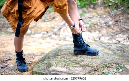 Woman hiking tying shoelace on forest trail, soft and select focus