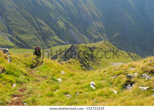 Woman hiking uphill in the mountains
