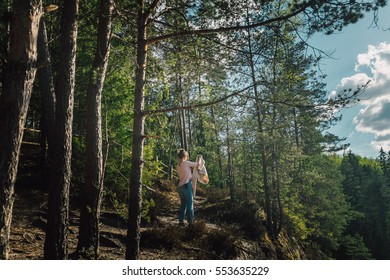 Woman hiking in woods, warm summer day.