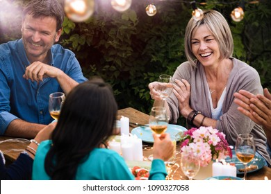 a woman in his forties a glass of wine by hand sits at a table in the garden with his friends for dinner.