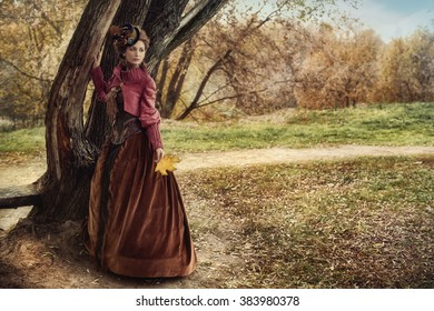 Woman in historical dress near the tree in autumn forest.