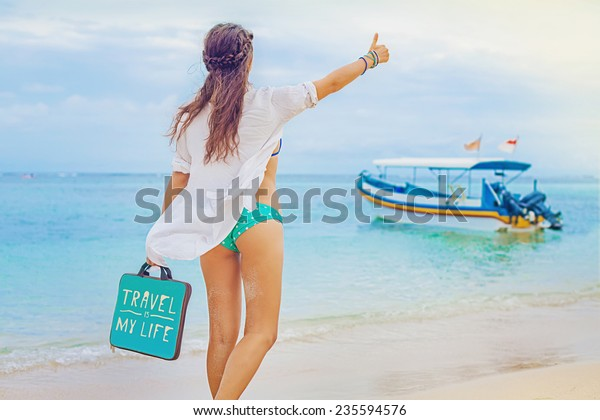 woman hitchhiking on a beach (back view, faceless)