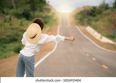 Woman hitchhiking on the road, empty rural curve, asphalt road way. Rear view.