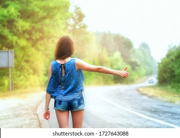 woman hitchhiking on road in forest, hitchhiking with thumbs up in a countryside road, Traveling and hitchhiking concept.
