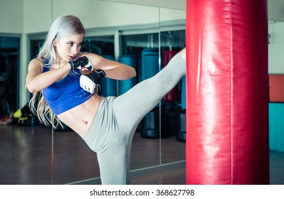 Woman hits the heavy bag with a strong kick. Concept about fit boxe, martial arts and sport