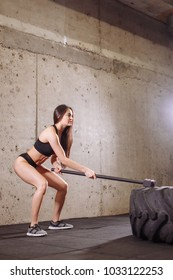 woman Hits Tire with sledgehammer, workout at gym with hammer and tractor tire