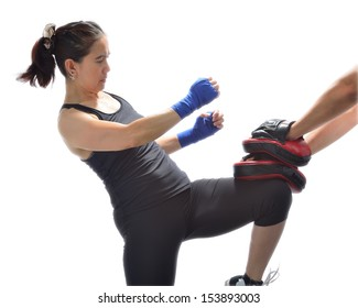 Woman hitting boxing pads with a knee.Thai boxing technique.