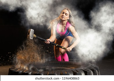 Woman hitting wheel tire with hammer sledge. Fitness training