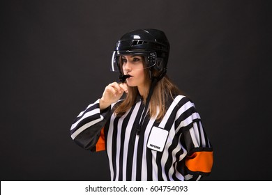 Woman hockey judge whistles into the whistle