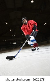 Woman hockey player skating on ice lining up to shoot puck.