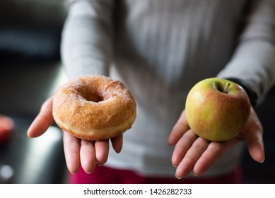 woman hold an apple and donuts at home, concept of healthy