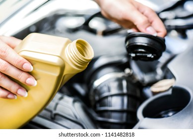 Woman hold basket and tap and going to change motor oil on car engine. Pour yellow liquid into vehicle.