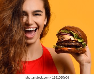 Woman hold big beef burger sandwich with egg with hungry mouth happy screaming laughing on yellow background. Fast food concept.