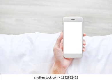woman hold blank screen smartphone on bed with space, Top view, Technology concept.