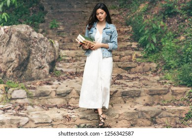 Woman hold books in hand ,walk down stone steps at nuture park,after read book and relexing.