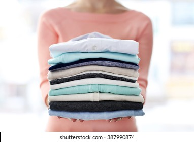 Woman hold clothes pile, close up