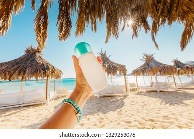Woman hold cream on the beach, sea background, Greece