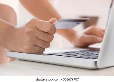 Woman hold Credit Card on laptop waiting for online shopping