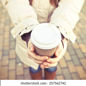 Woman hold cup of coffee on stree