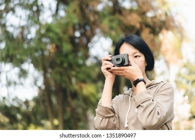 woman hold a digital camera at the park