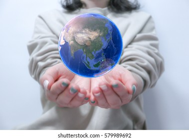 a woman is hold earth on the hand and the globe is shown asia
