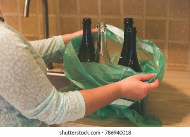 Woman hold garbage bag with empty glass bottles in the kitchen, recycling.
