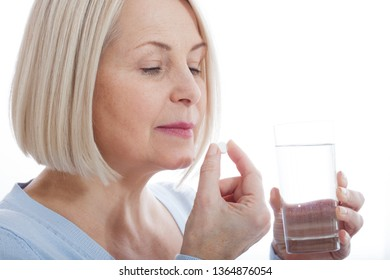 Woman hold glass still water and pill. Sick woman taking putting pill in mouth painkiller or antibiotic medicine, depression treatment chronic disease or biologically active supplement concept