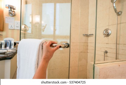 woman hold handle bathroom cabin with left hand