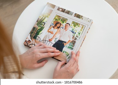 woman hold in hands photo book (paper with a grainy structure) from family pregnancy photo shoot. beautiful and convenient storage of photos. memory of important period.