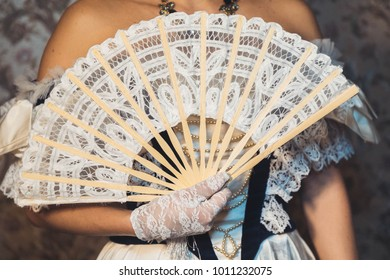 Woman hold  a lacy fan in openwork gloves