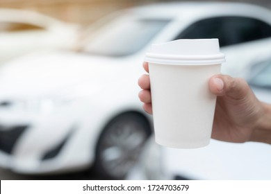 Woman hold paper cup coffee of hot in hand while standing car on the side before driving a vehicle in the morning sunlight. transportation and vehicle concept.
