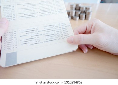Woman hold passbook on hand, coins background