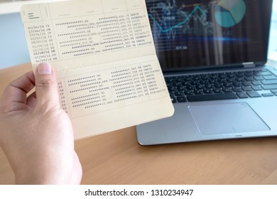 Woman hold passbook on hand,laptop background