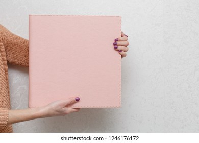 Woman hold a photo album  photo book with  leather cover unfolded photobook background for photo publishing sample photobook the person is looking at a photobook