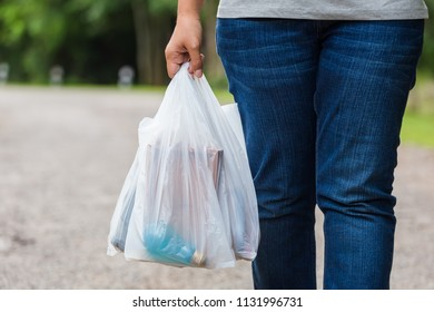 Woman hold the plastic bags and walk on the street in the park