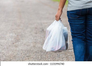 Woman hold the plastic bags and walk on the street